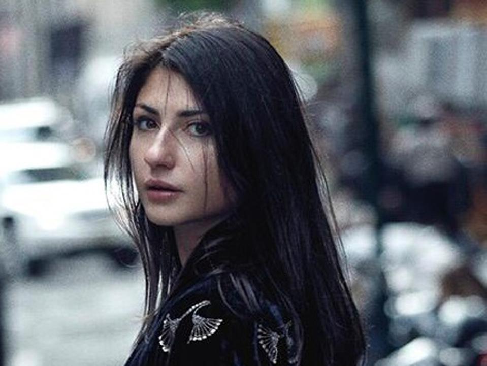 Headshot of Mella with long black hair walking on city street.