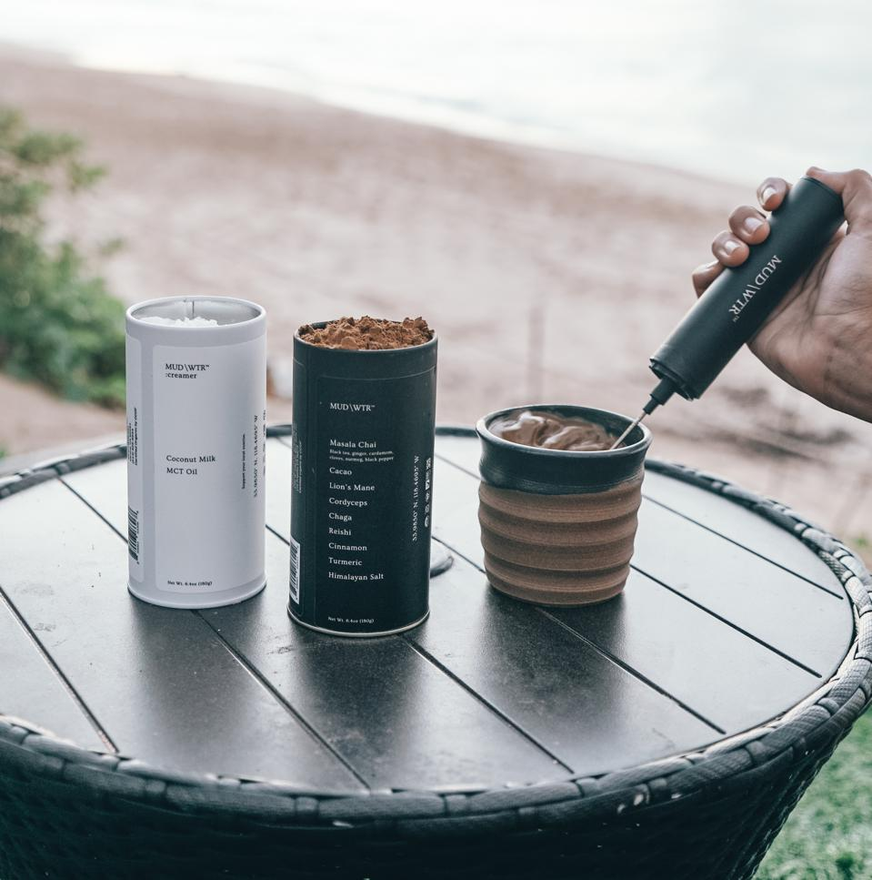 A beachfront set up of MUD/WTR and accessories