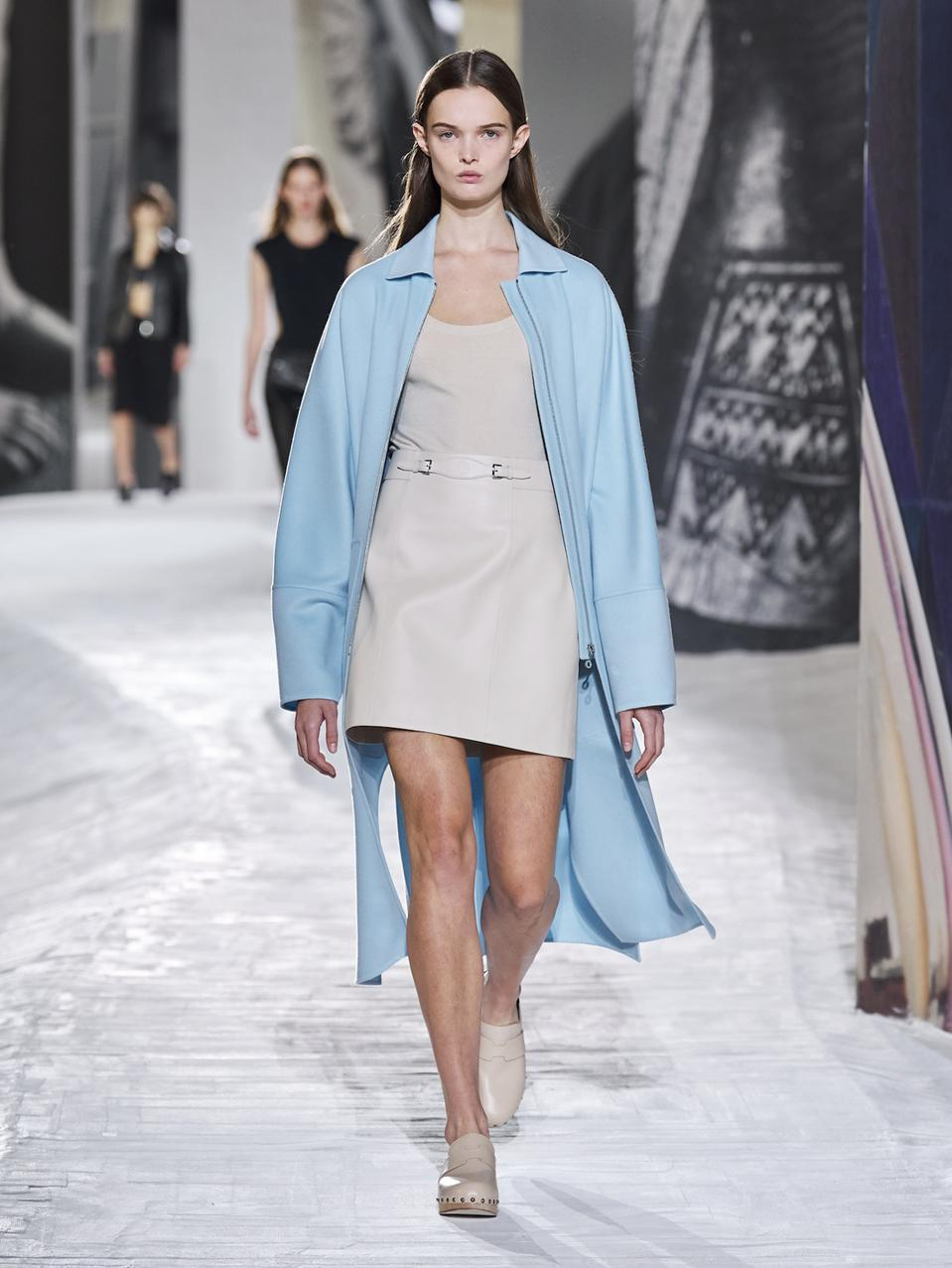 A zipped coat, in double-face cashmere, in coastal blue, with swivel clasp zip pulls, in palladium-finish metal. A vest bodysuit, in stretch silk knit, in Poros white. A micro skirt, in glossy lambskin, in Poros white. A pair of clogs in calfskin, in beech brown, with sole in beechwood, and stud details, in palladium-finish metal.