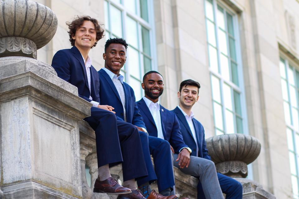 Four handsome, young men sitting on a stone rail.