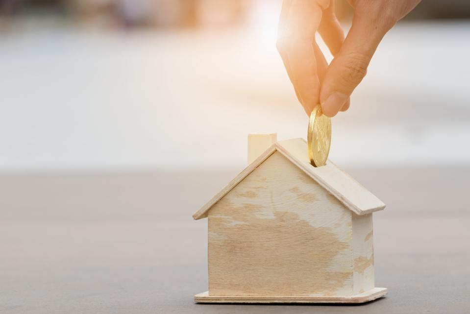 Cropped Hand Putting Gold Coin In House Shaped Piggy Bank On Table