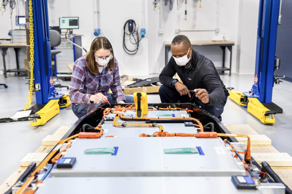 Dane Hardware, Ford Motor Co. design and release engineer, and Mary Fredrick, Ford Motor Co. battery validation engineer, measure the voltage of a battery using a digital multi-meter at Ford's Battery Benchmarking and Test Laboratory in Allen Park, Michigan. Since this battery is not connected to a test setup, the meter is used to confirm the battery voltage and check isolation.