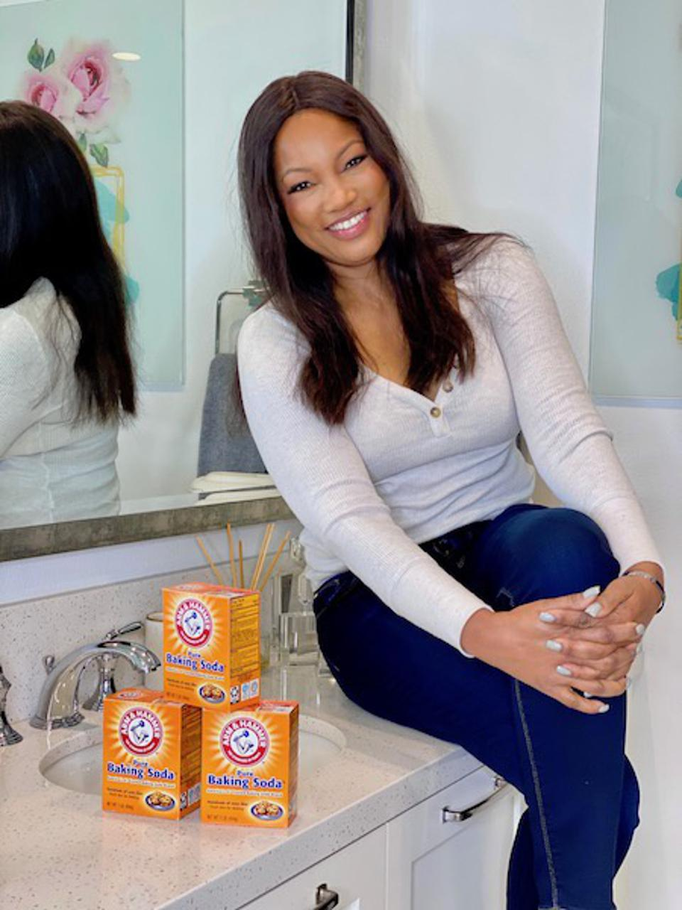 Garcelle Beauvais sitting on a bathroom coutertop with three boxes of Arm and Hammer Baking soda