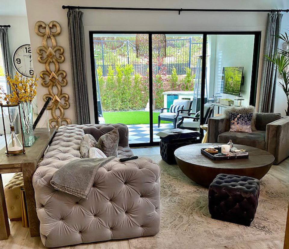 A living room with a grey sofa and wood coffee table next to a window.
