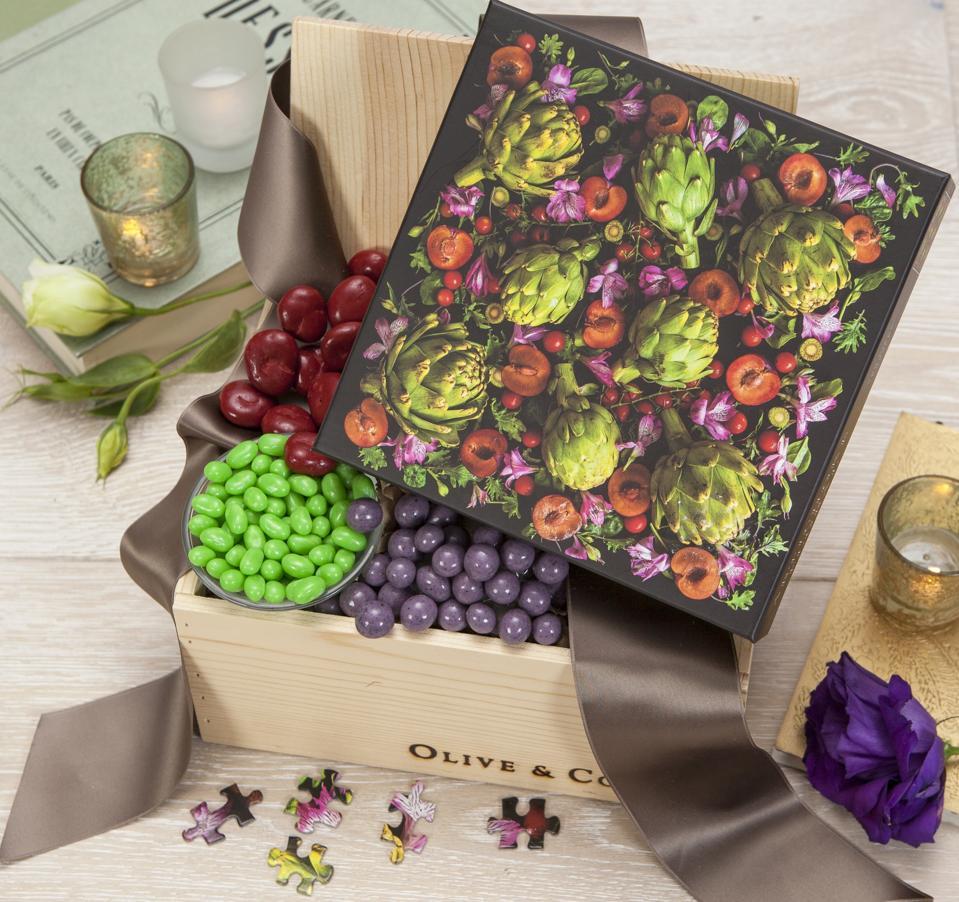 Un puzzle sur le thème du jardin avec des artichauts et des fleurs se trouve dans une boîte
