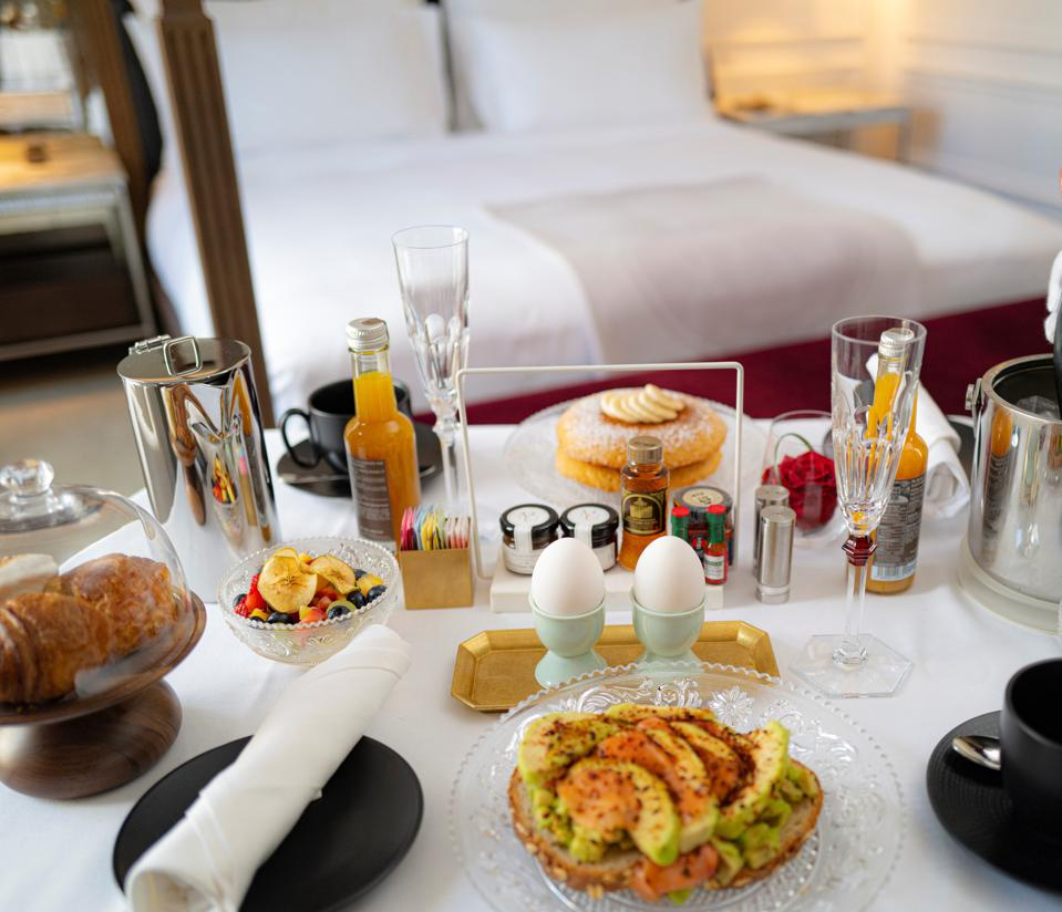 A table of elaborate breakfast preparations with a four poster bed in the background