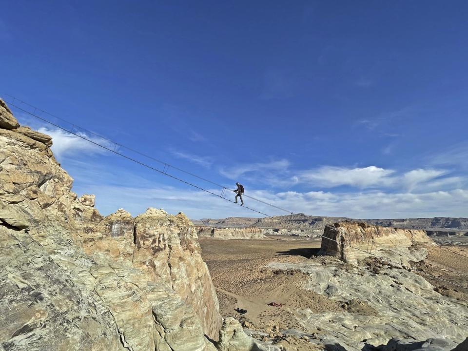 A staircase suspended between two rock formations 400 feet in the air above the Utah desert
