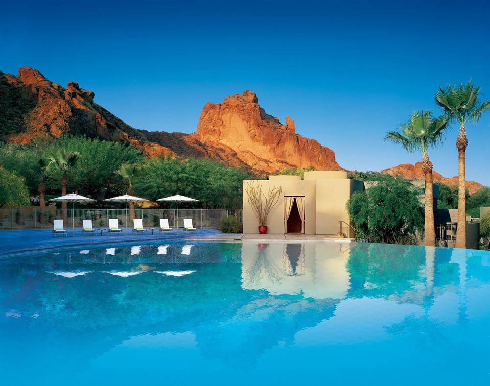 A swimming pool with a large red rock formation behind it