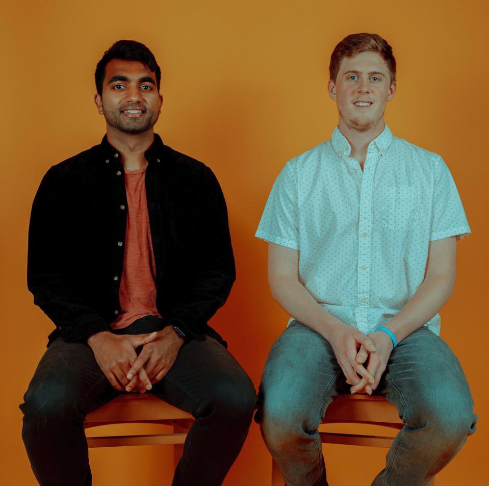 Two gentlemen sitting on orange chairs.
