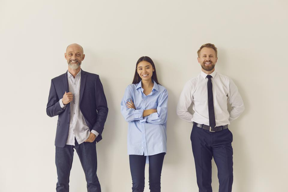 Three cheerful multi-aged office workers leaning against wall and looking at camera