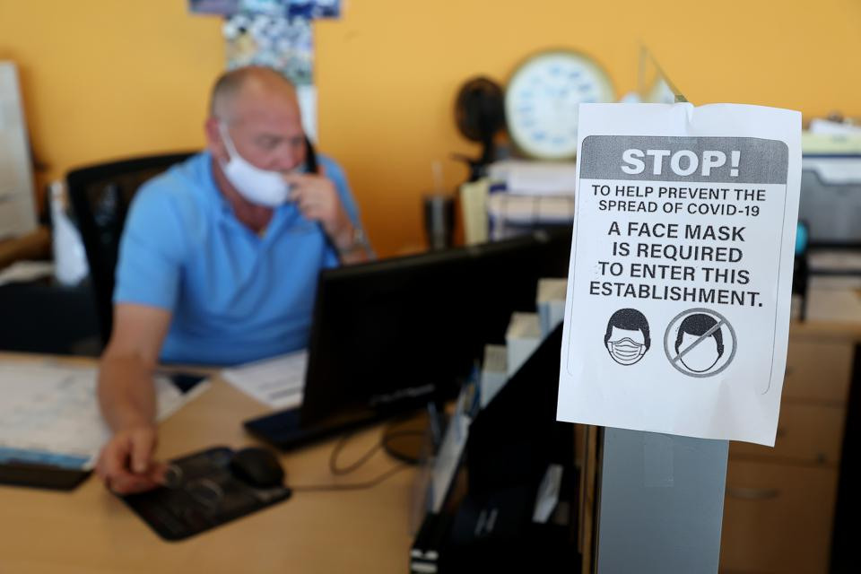 Auto dealership displays a sign saying masks are required due to COVID-19.