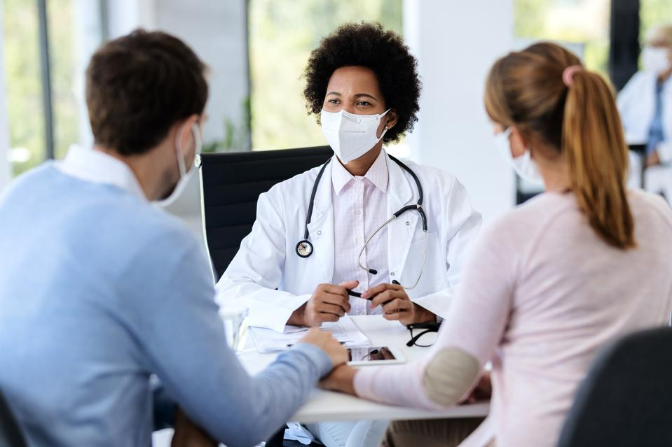 Couple talking to their doctor