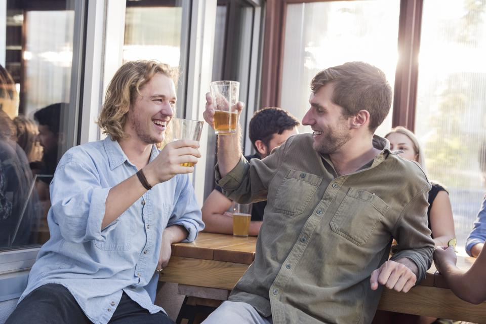Male friends toasting beer glasses at pub