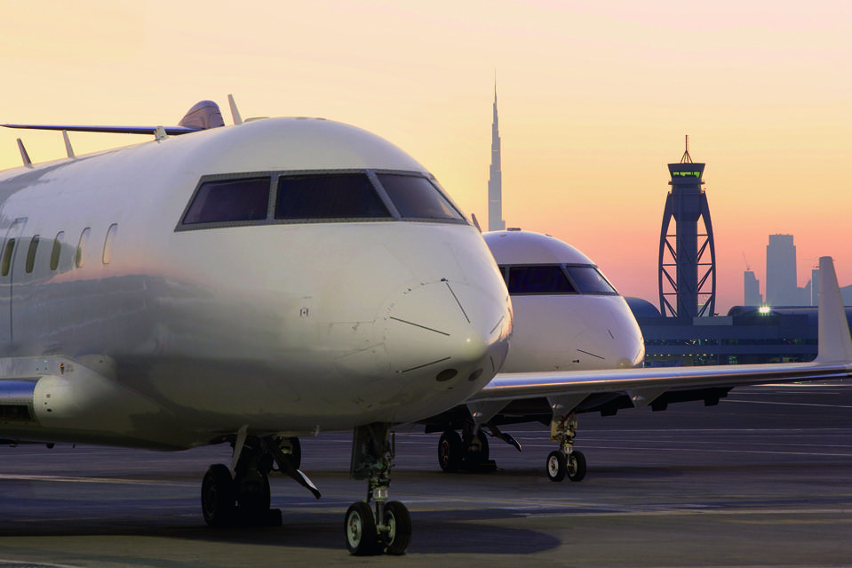 Two Luxaviation jets parked on the runway in Dubai at sunset.