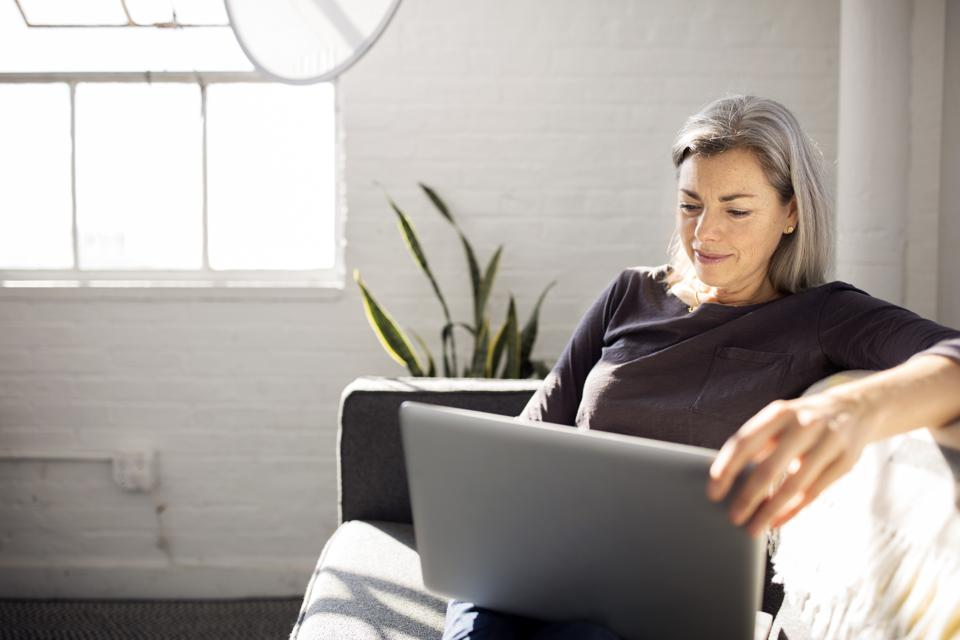 Woman using laptop while sitting on sofa in living room at home