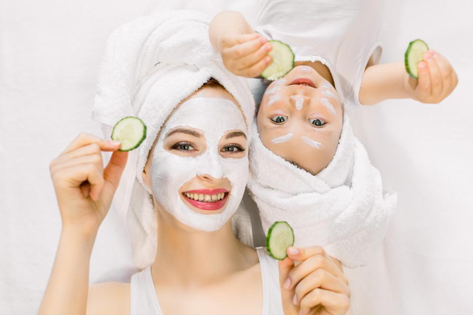 Mother and daughter in white shirts and white towels on their heads in a home bathroom, doing spa procedures with mud mask and fresh cucumber slices. Family time, spa and beauty, mothers day