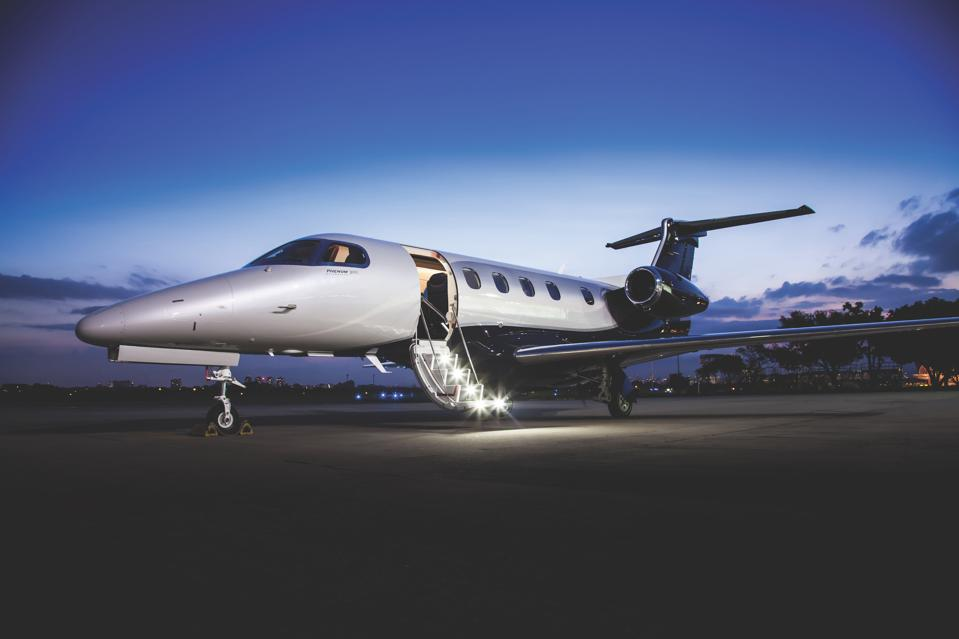 Private jet on tarmac at dusk with air stairs deployed