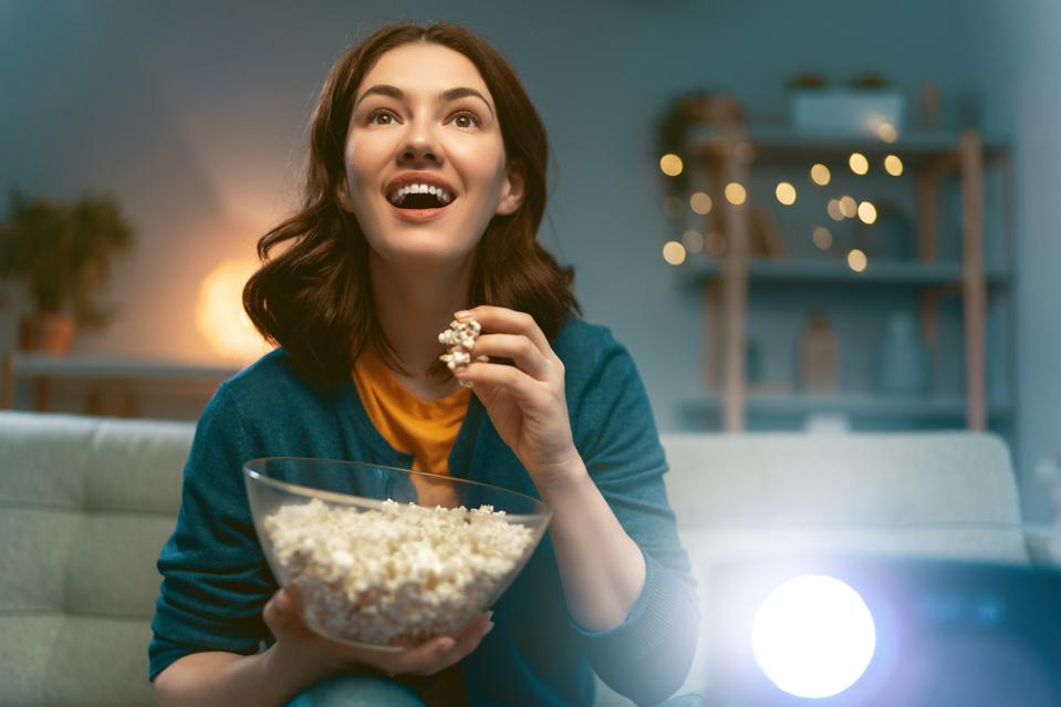 Young person watching movies with popcorn in the evening at home.