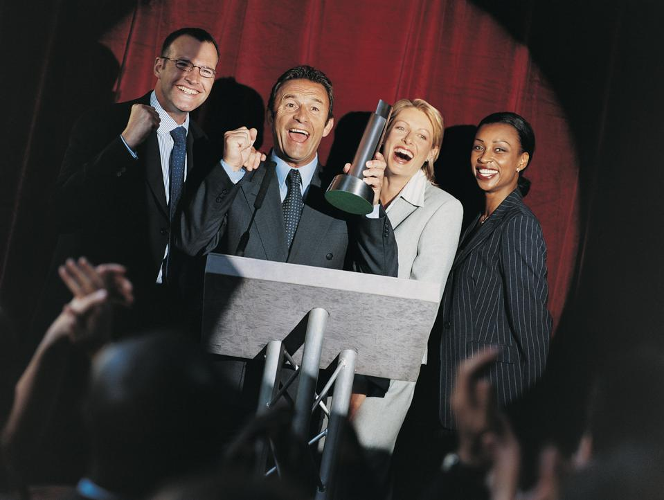 Businesspeople on stage, in the spotlight