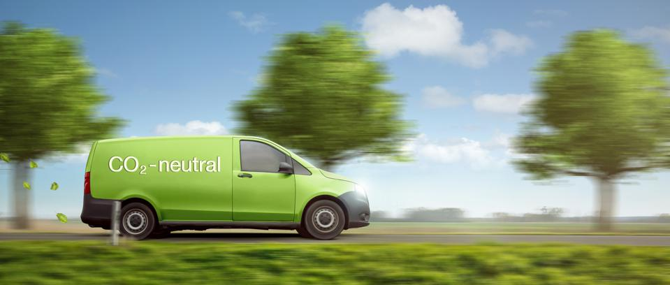Carbon-neutral delivery with a green van driving on a country road with green trees