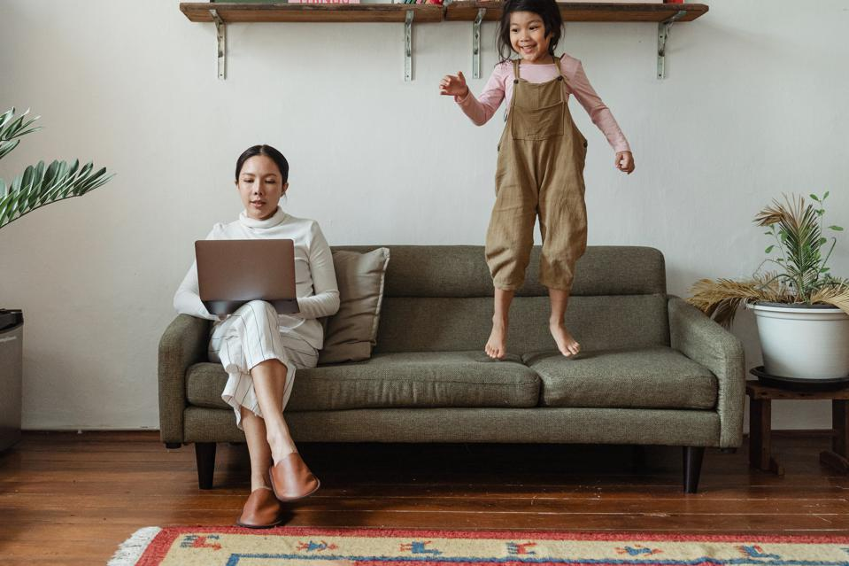 mom on couch using laptop with daughter jumping on couch next to her