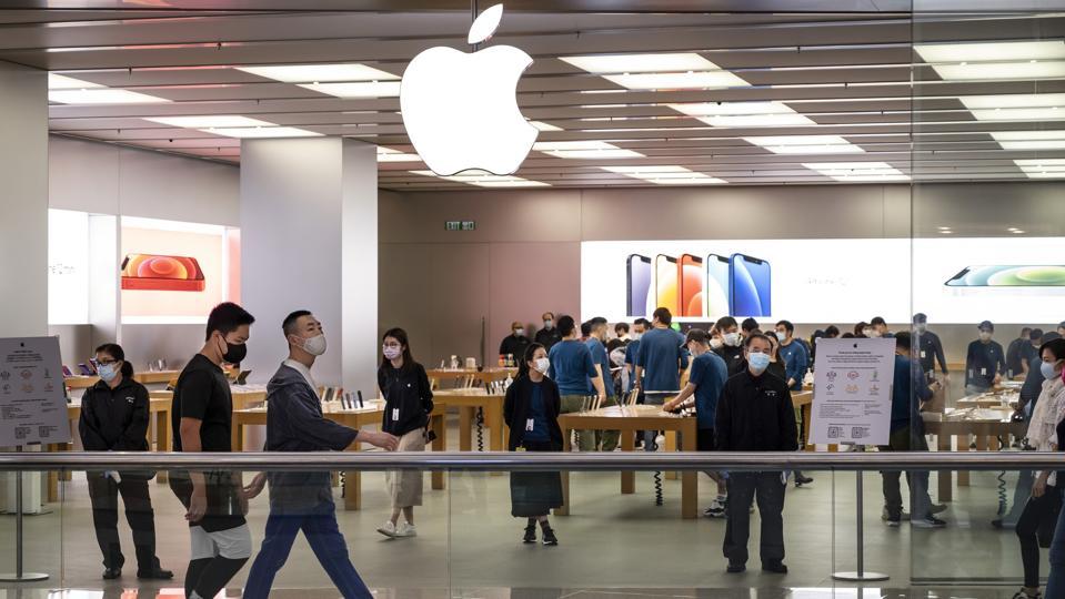 Shoppers walk past an American multinational technology...