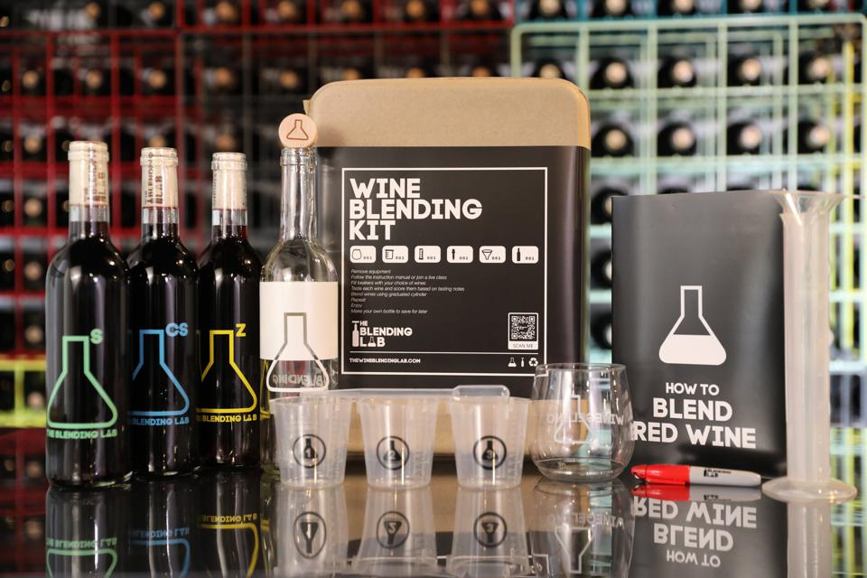 three mini bottles of wine and a kit to blend them are all together in a kit