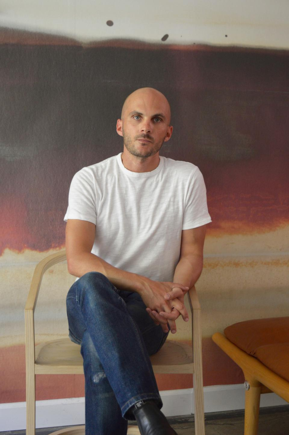 A man with a shaved head, wearing a white t-shirt and jeans, sits in a chair with his legs crossed.