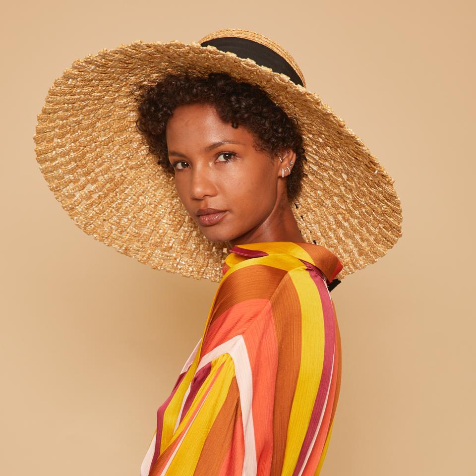 Une femme vêtue d'un chemisier aux couleurs vives porte le chapeau de paille naturelle Mirabel