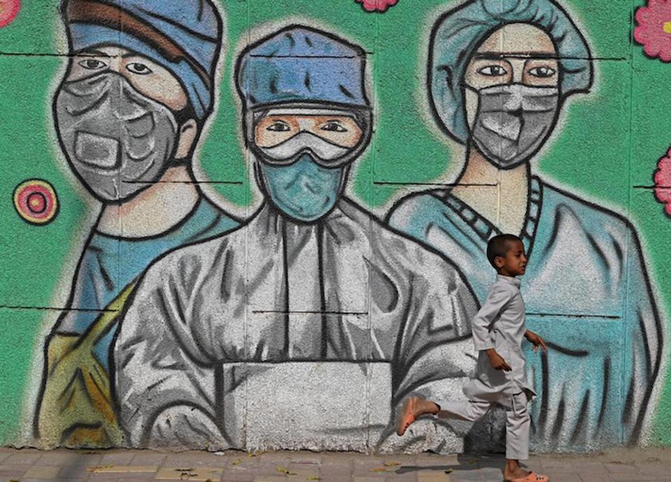 On March 21, 2021, a child runs past a mural depicting frontline health care workers, along a road in New Delhi, India.