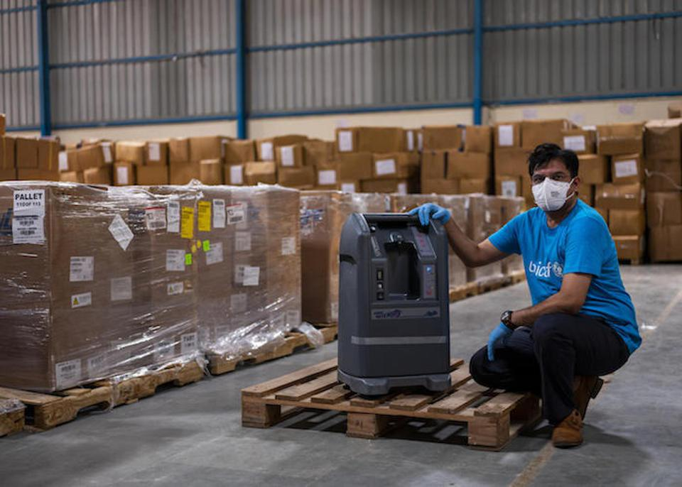 A UNICEF worker examines a shipment of oxygen concentrators in Delhi, India.
