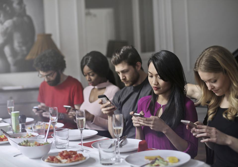 Friends looking at their phones while having dinner.