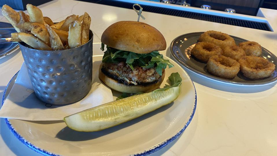 A plate with a burger, pickles, and fries on it, and a second plate with onion rings