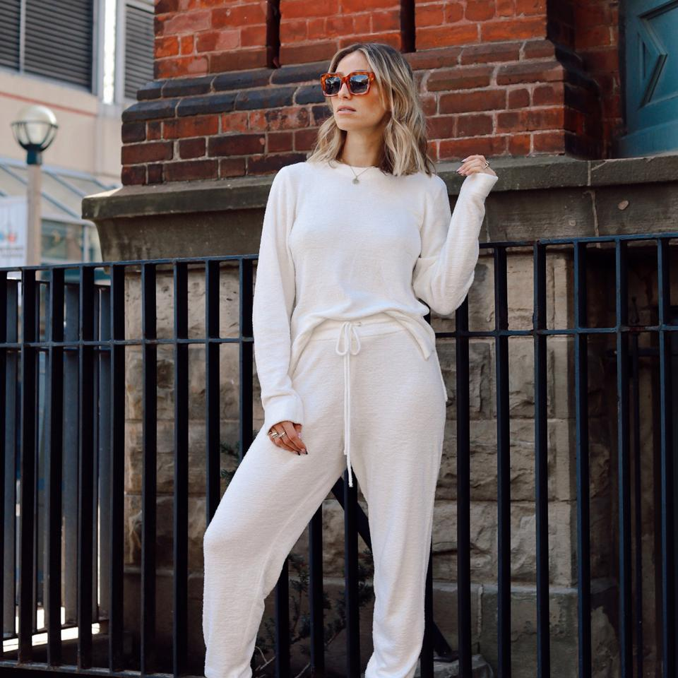 A woman wearing Knix Cozzzy crew top and track pant matching set.