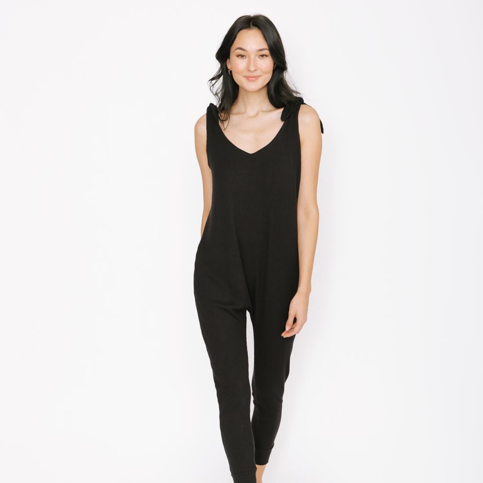 A woman wears a black Smash + Tess romper.
