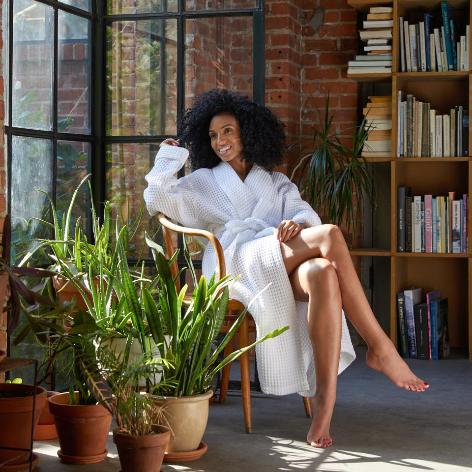 A woman sits in a chair wearing a white Brooklinen waffle robe.