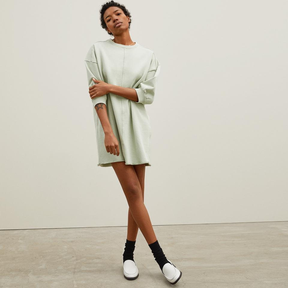 A woman wears the Everlane Track Dress.