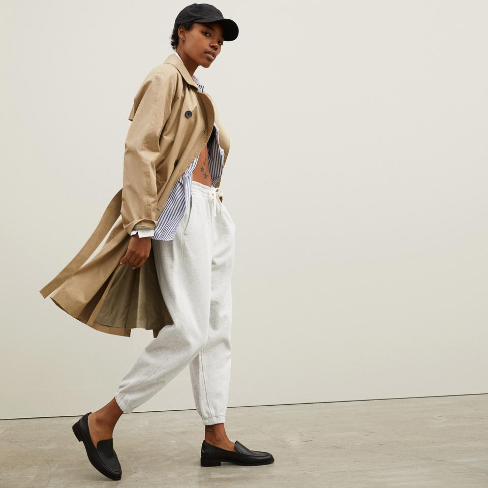 A woman models Everlane sweatpants and a trench coat.