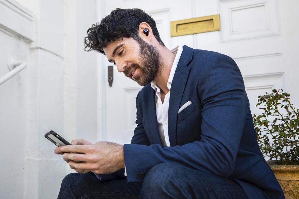 Man outside a front door wearing Lypertek PurePlay Z7 earphones