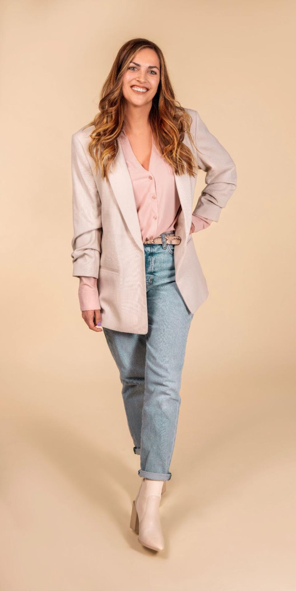 A white woman with long hair poses wearing jeans and a pink shirt and tan blazer.