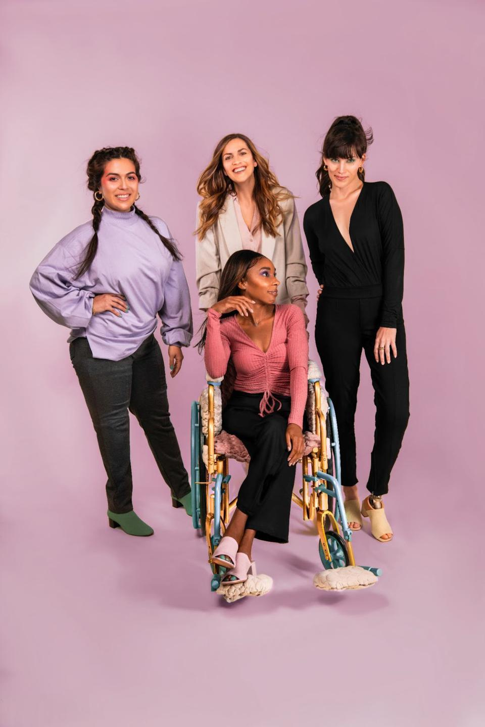 Four women, one in a wheelchair, pose. The background is pink.