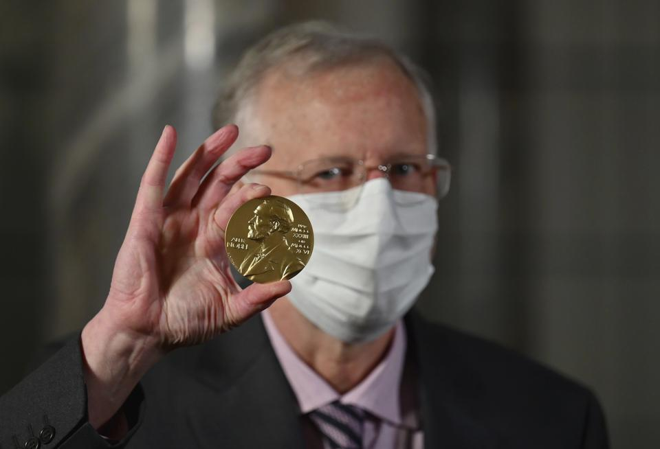 Virologist Charles M. Rice poses with his Nobel prize medal.