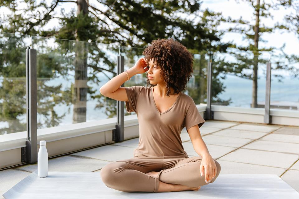 A woman sits on a yoga mat in a beige Smash + Tess romper.