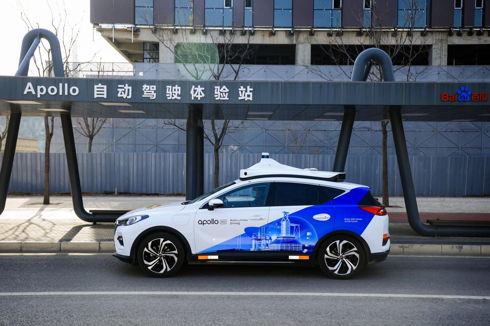 A Baidu Apollo robotaxi SUV parked on a curb in China.