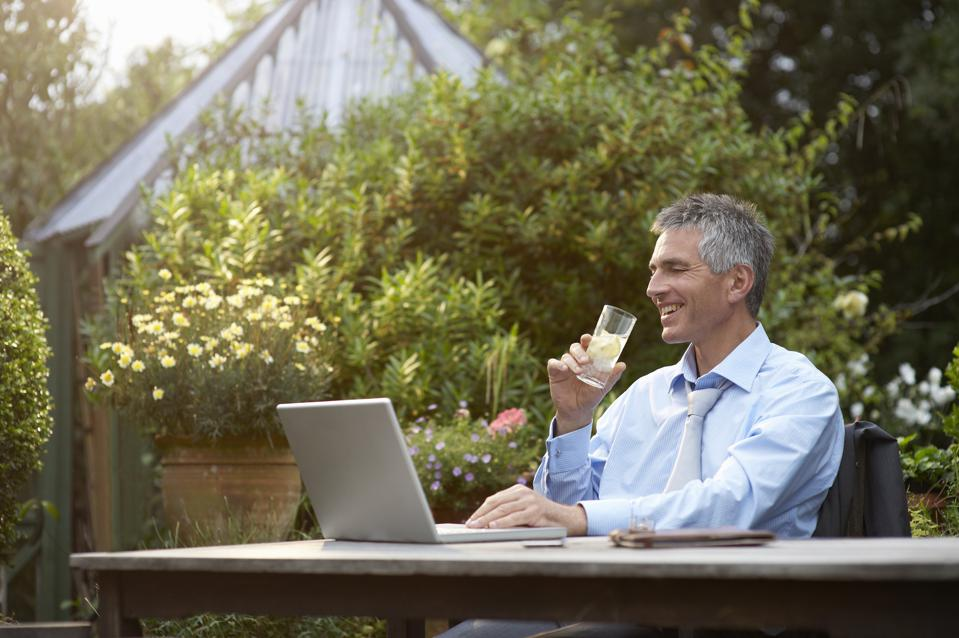 Man with drink and laptop in garden.