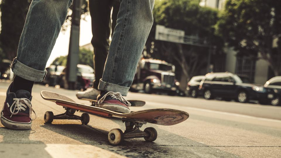 Close-up of man with skateboard on sidewalk