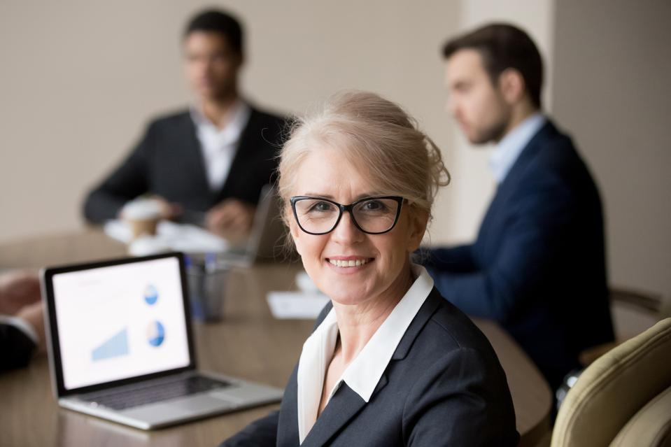 Happy middle-aged businesswoman in glasses posing at team office meeting