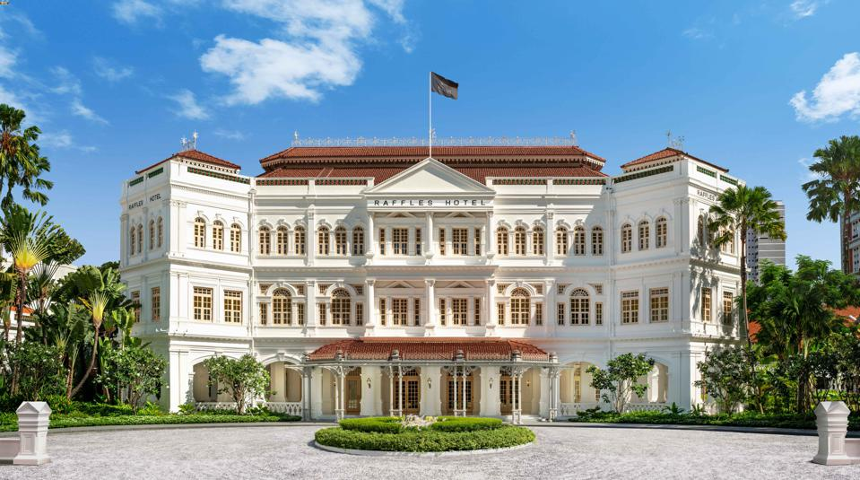 The gleaming white Raffles Hotel Singapore sits behind a large circular driveway.