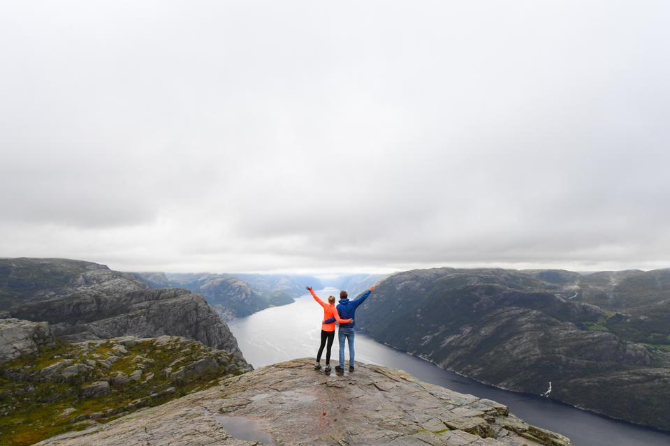 Couple standing on the edge of Preikestolen cliff in southwest Norway.