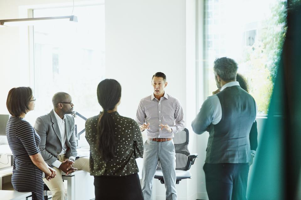 Businessman leading discussion with project teammates during meeting in office